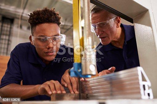 istock Carpenter Training Male Apprentice To Use Mechanized Saw 628110826