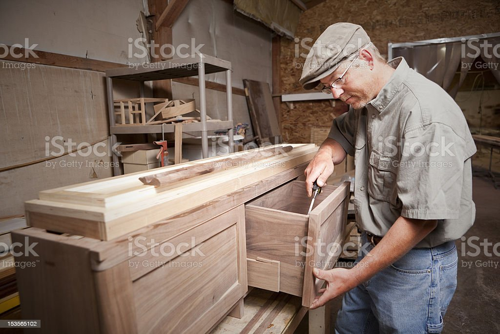 Carpenter uses chisel (tool) on cabinet drawer - Royalty-free Business Stock Photo
