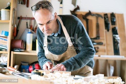 Carpenter using a chisel to refine rebate.