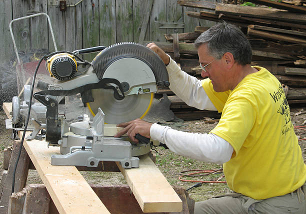 Carpenter using a chop saw stock photo