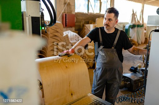 Focused mid adult male carpenter holding a wooden part on a CNC mschine and adjusting speed on a computer panel at furniture factory