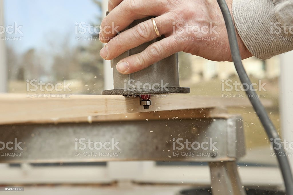 Carpenter Using a Router to Round Trim Board stock photo