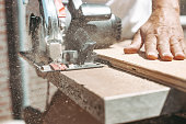 istock Carpenter using circular power saw for cutting wood, home improvement, do it yourself (DIY) and construction works concept, action shot 1269034556
