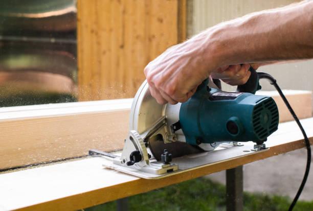 Tischler mit Kreissäge schneiden Holzbretter mit Hand-Elektro-Werkzeuge. – Foto