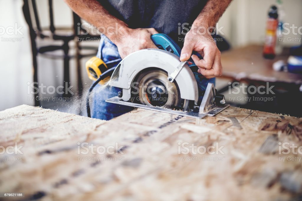 Carpenter using circular saw for cutting wooden boards. Construction details of male worker or handy man with power tools royalty-free stock photo