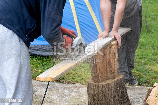 Carpenter using circular saw cutting wooden boards with hand power tools.