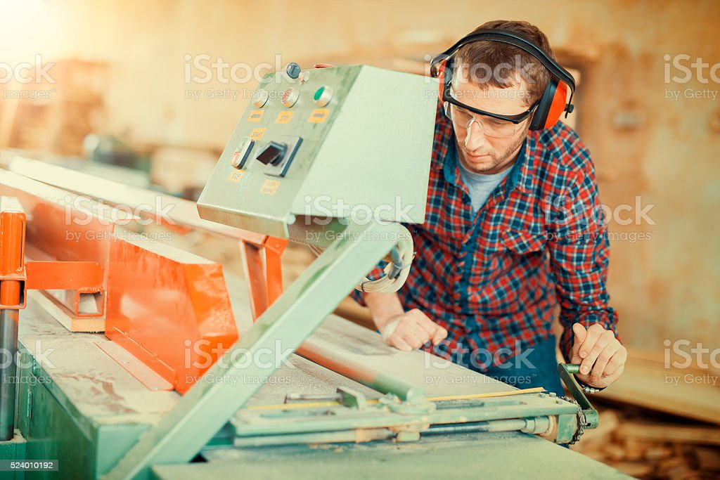 Carpenter using circular saw in his workshop stock photo