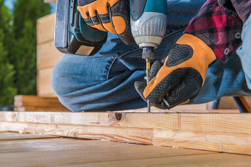 Male Carpenter Using Cordless Drill To Drive Long Screw Through Wooden Planks.