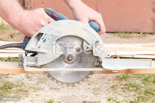 istock Carpenter using electrical powered circular saw to cut wooden plate. 591994522