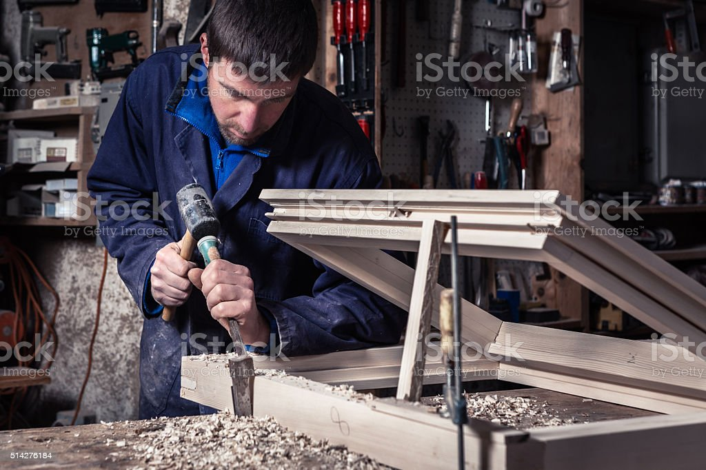 Carpenter using Hammer and Chisel in Workshop stock photo