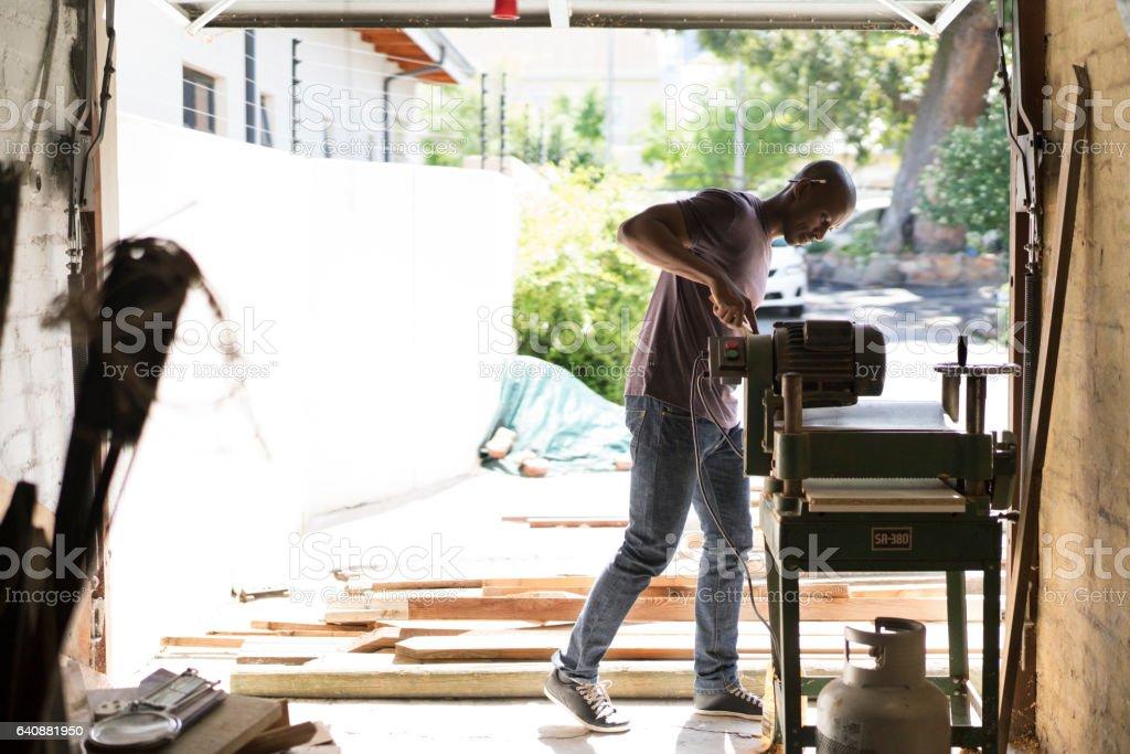 Carpenter using machinery at workshop stock photo