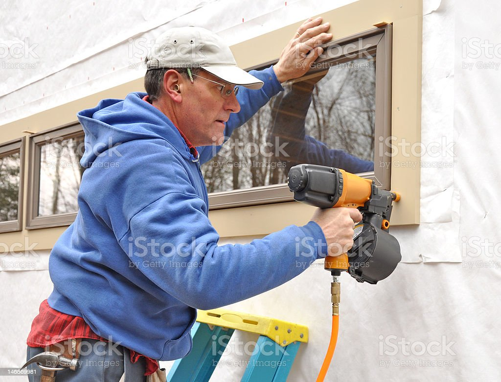 Carpenter using nail gun stock photo