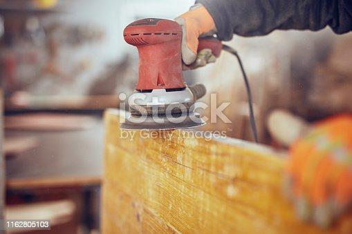 Carpenter using orbital electric sander in a retro vintage workshop.
