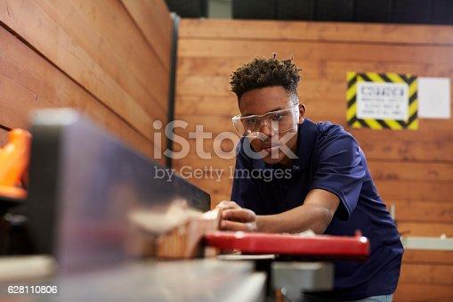 istock Carpenter Using Plane In Woodworking Woodshop 628110806