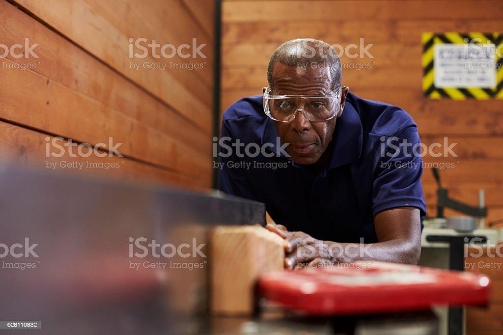 Carpenter Using Plane In Woodworking Woodshop stock photo