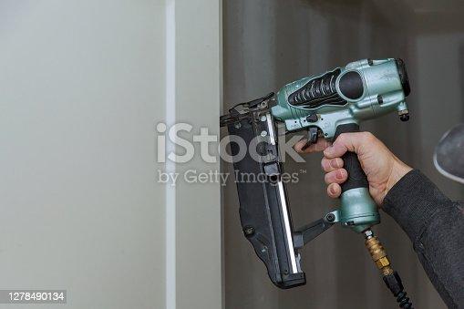 istock Carpenter using pneumatic nail gun installation of install the door new 1278490134