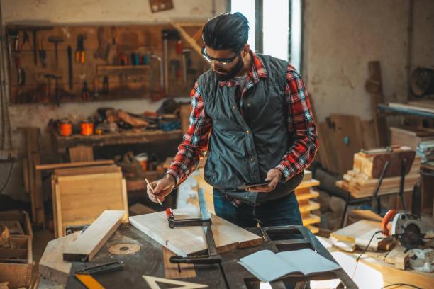 tischler mit tablette während der arbeit in seiner werkstatt auf möbel-projekt - tattoo maker online stock-fotos und bilder