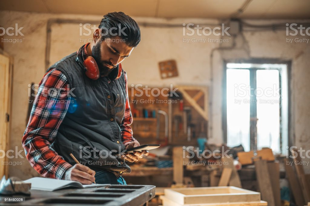 Carpenter using tablet while working in his workshop pn furniture project stock photo