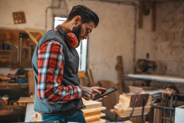 tischler mit tablette während der arbeit in seiner werkstatt-pn-möbel-projekt - tattoo maker online stock-fotos und bilder