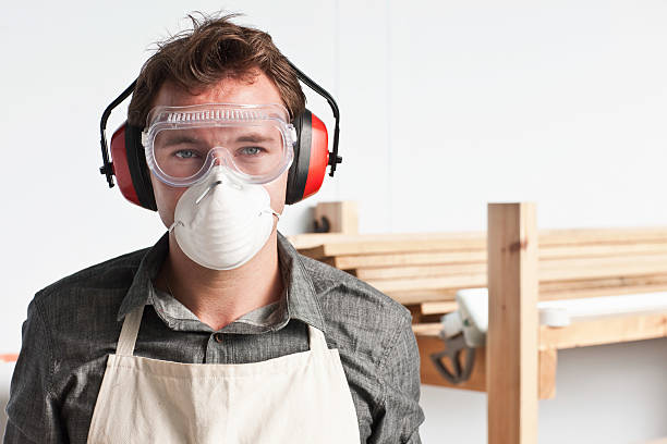 Carpenter wearing dust mask and ear defenders, portrait London,UK, pollution mask stock pictures, royalty-free photos & images
