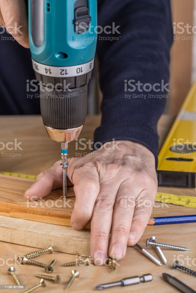 A man holds a cordless screwdriver in his hand and wraps the screw in...