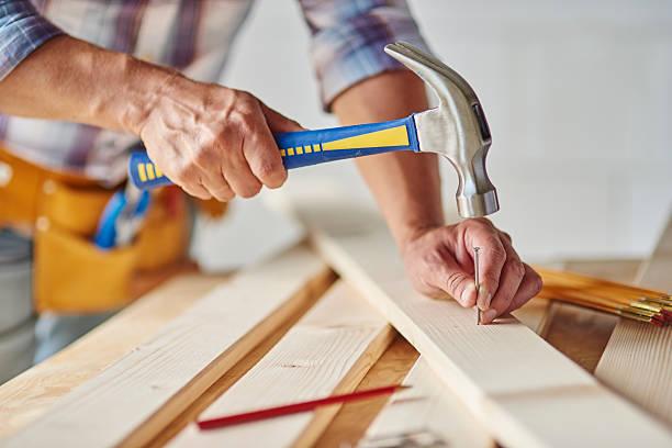 Carpenter with hammer hitting nails Carpenter with hammer hitting nails nail work tool stock pictures, royalty-free photos & images