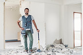 istock Carpenter with hammer standing in abandoned room 860088740