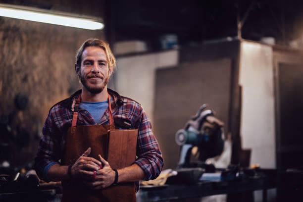 tischler mit online-business tablet halten und stehen in werkstatt - kaffeetasse tattoo stock-fotos und bilder