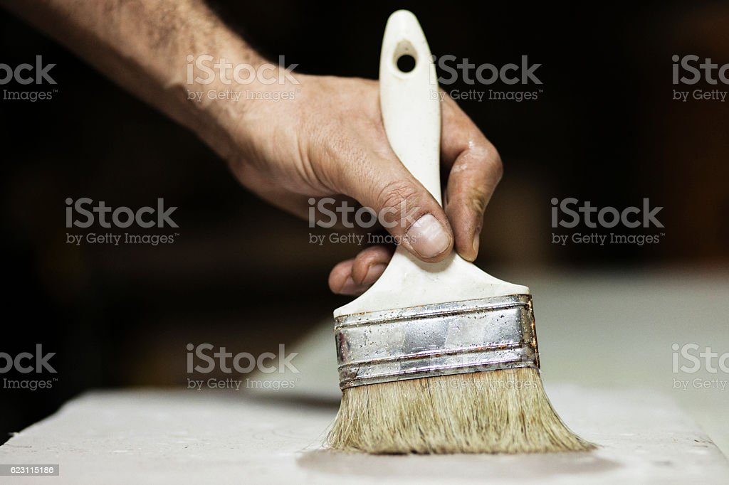 Carpenter with paint brush painting a piece of plate stock photo