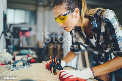 Manual worker with protective workwear working in the carpentry studio