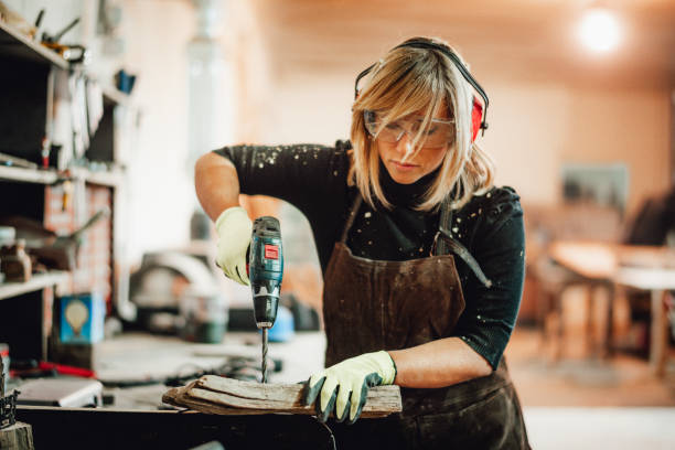A carpenter woman changing an orbital sander's paper while working in a shop stock photo