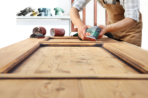 1015564946 istock photo carpenter work the wood with the sander 968260124