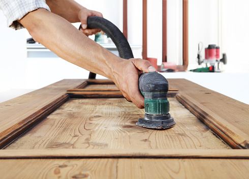 1015564946 istock photo carpenter work the wood with the sander 968260126