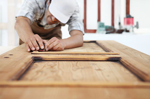 1015564946 istock photo carpenter work the wood with the sandpaper 1015564930