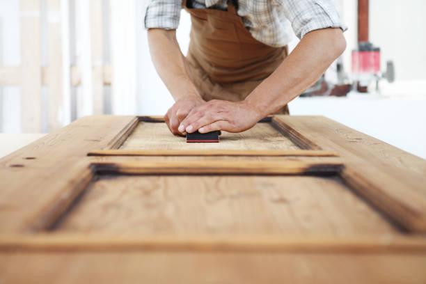menuisier travaille le bois avec du papier de verre - ameublement photos et images de collection
