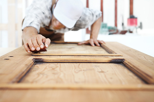1015564946 istock photo carpenter work the wood with the sandpaper 968260154