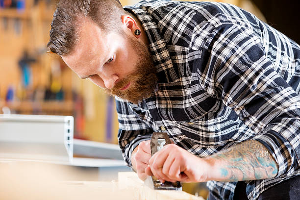 schreiner arbeiten mit flugzeug auf holz plank in workshops - baroque tattoo stock-fotos und bilder