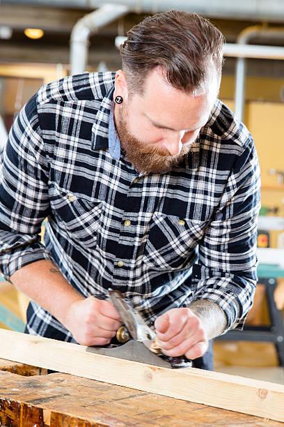 schreiner arbeiten mit planer auf holz plank in workshops - baroque tattoo stock-fotos und bilder