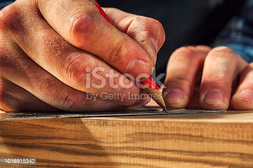 Close-up The man measures a wooden board  and marks with pencil the necessary points for slices