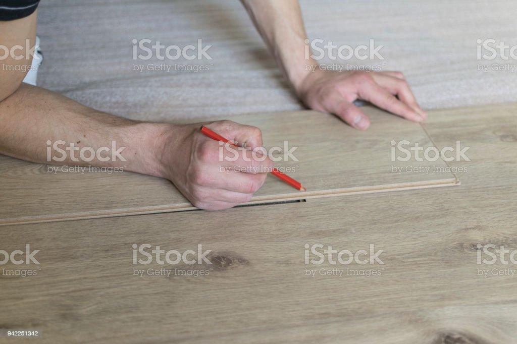 Carpenter Worker Installing Laminate Flooring In The Room Stock