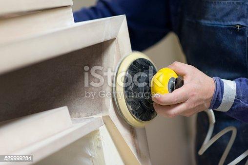 530997702istockphoto Carpenter Worker Sanding Wooden Table with Power Sander 529999284