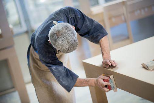 530997702 istock photo Carpenter Worker Sanding Wooden Table with Sander 529998972