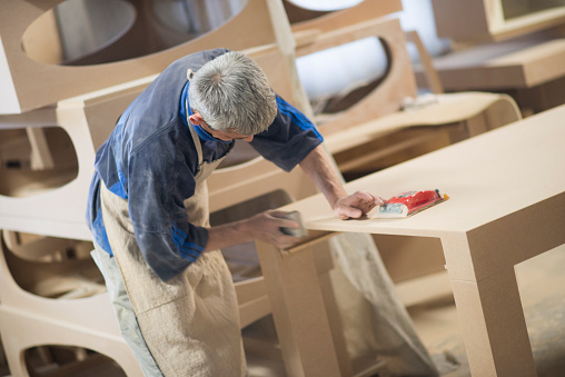 530997702 istock photo Carpenter Worker Sanding Wooden Table with Sander 530997702