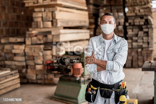 "Happy Latin American carpenter working at his workshop wearing a facemask to avoid coronavirus -"" pandemic lifestyle concepts"