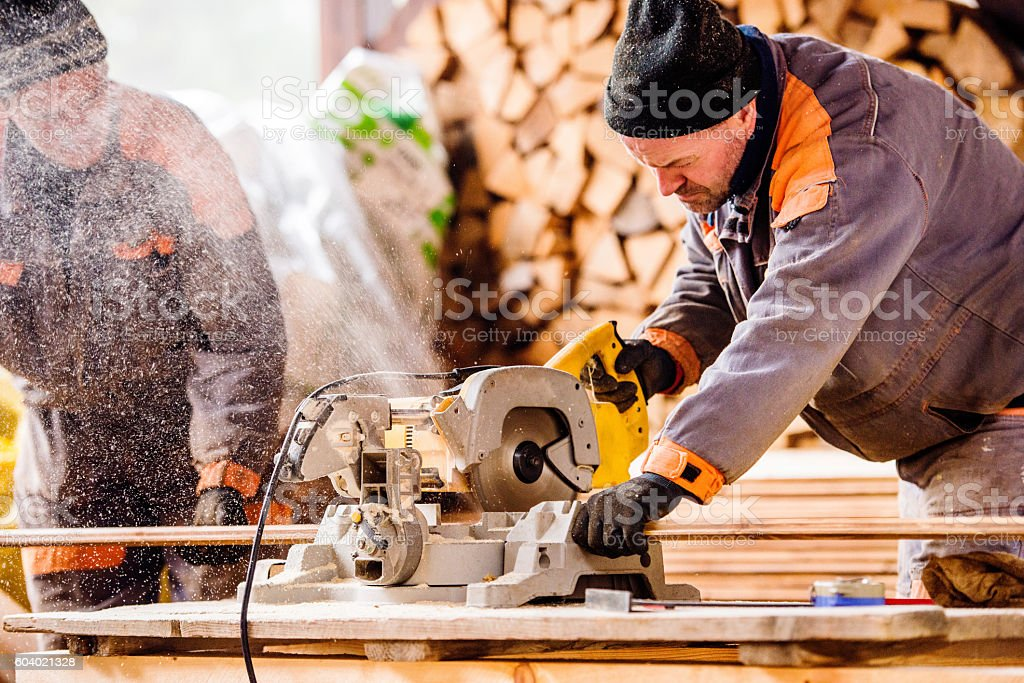 Carpenter working. Man cutting plank by circular saw. stock photo