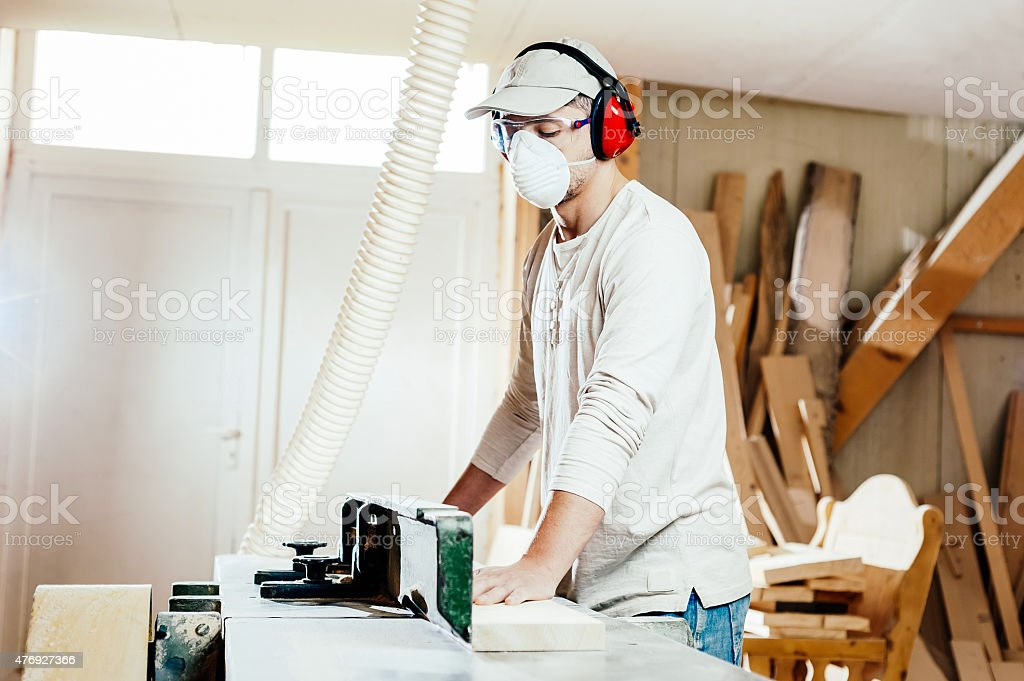 Carpenter working on wood machine in factory stock photo