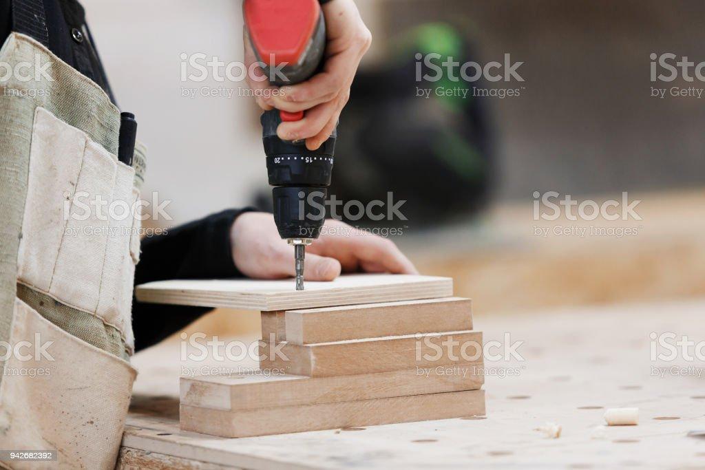 Tischler arbeiten mit einem Akkuschrauber auf der Werkbank. Nahaufnahme, konzentrieren sich auf das Werkzeug – Foto