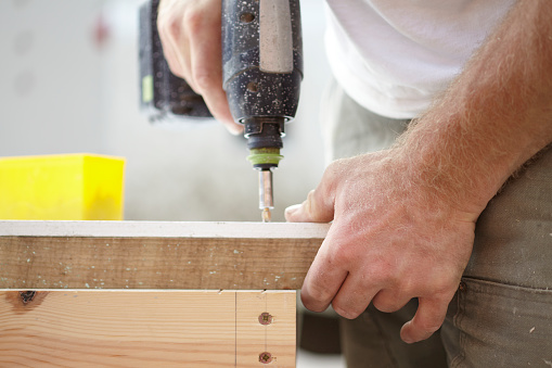 Close up of a carpenter using a cordless electric drill power tool