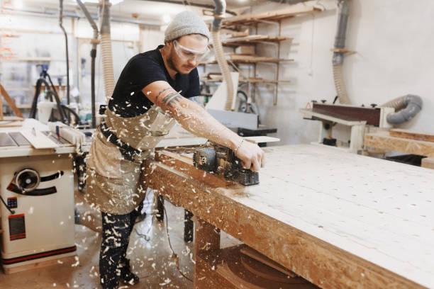 tischler arbeiten mit elektrischen hobel auf holzbrett in werkstatt. handwerker macht eigenen erfolgreichen kleinunternehmen. - schreiner stock-fotos und bilder