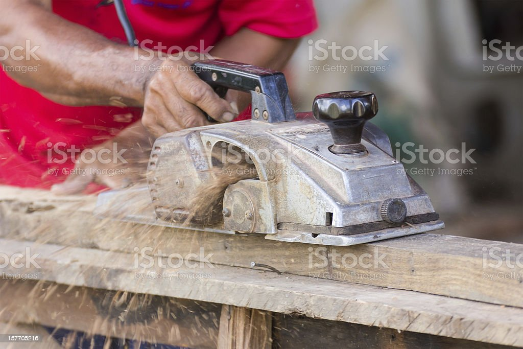 Carpenter working with electric planer royalty-free stock photo